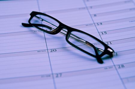 Pair of reading glasses folded on top of calendar Zdjęcie Seryjne