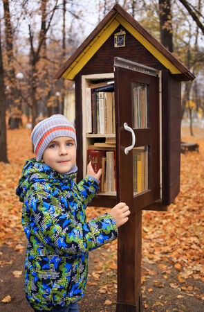 curiousness: Boy opening a case with books staying outdoors.  Autumn yellow trees on the background.