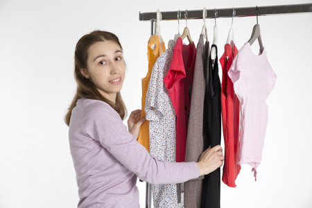 coat rack: young woman chooses clothes on , isolated on coat rack white background