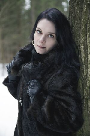 Brunette girl wearing a fur coat in winter forest photo