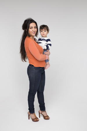 armenian woman: Brunette mother with her child on a white background