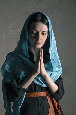 Beautiful young woman in shawl praying, studio shoot photo
