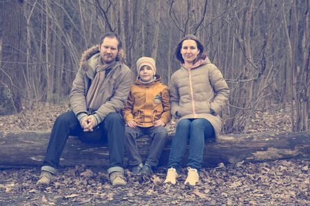 ifestyle: Happy family sitting over spring forest trees. Pleasure. Dreams. Toned and Filtered Photo.