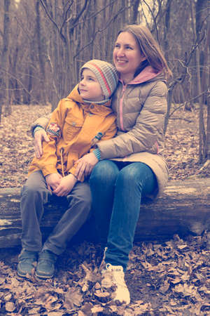 ifestyle: Happy young woman with her son over spring forest trees. Pleasure. Dreams. Toned and Filtered Photo. Stock Photo