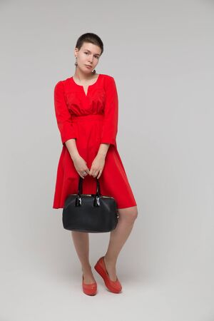 girl in red dress: Beautiful girl red dress posing in studio with bag, isolated on gray  Stock Photo