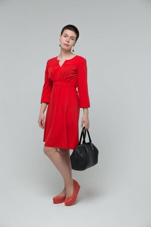 girl in red dress: Beautiful girl red dress posing in studio with bag, isolated on gray background