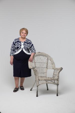 jovial: Senior Woman Relaxing near Chair Stock Photo
