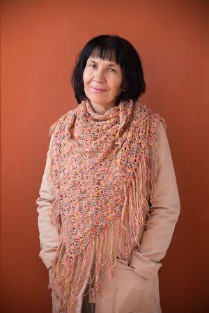 crocheted: Adult brunette woman wearing orange crocheted shawl Stock Photo