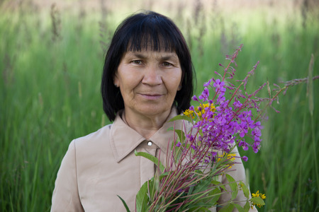 landlady: Senior brunette woman with willow-herb in field