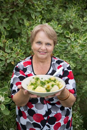 grandparent: Grandparent woman with boiled potatoes in the plate