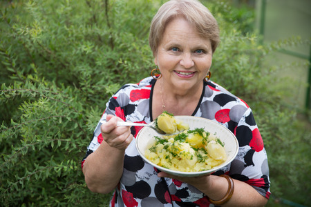 Grandparent woman with boiled potatoes in the plate