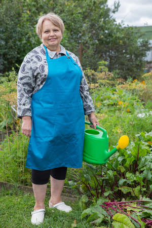 pensioner: Senior pensioner woman with watering can at dacha