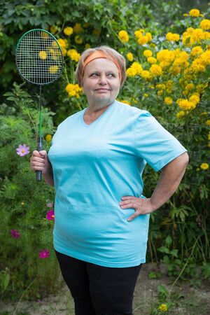 70s tennis: Sporty pensioner woman with racket