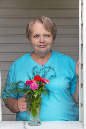 oldage: Pensioner woman at window with bunch of flowers