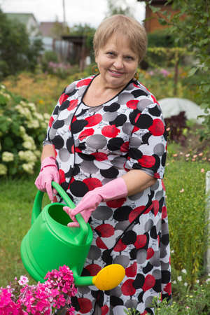 dacha: Senior pensioner woman with watering can at dacha