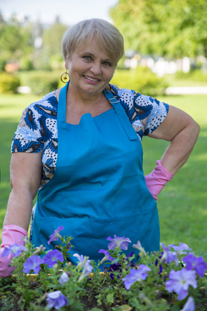 gloved: Happy senior woman gloved works in the garden with flowers
