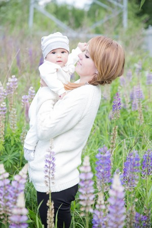lupins: Young mother with baby at meadow lupins flowers. Soft focus on baby