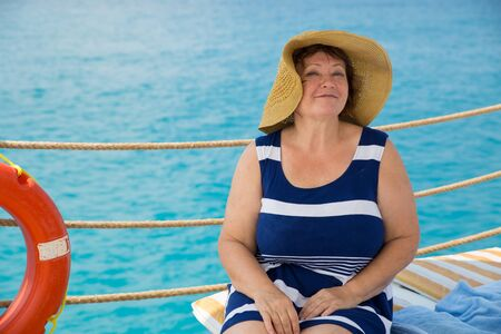 Smiling Senior woman wearing hat. Blue water on background