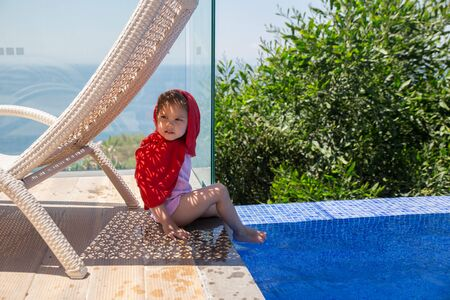 3 years old girl hiding from the sun in the shade of the lounger. She is wrapped in red cloth to protect against sunburn.