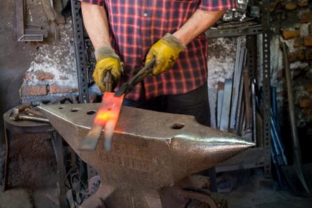 Hot iron forging on anvil. Handmade blacksmith