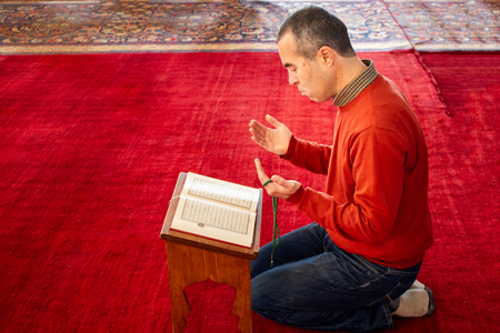 Muslim man reading the Quran at the mosque