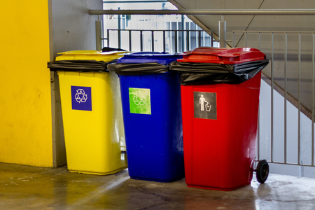 Yellow, blue, red recycle trash bin and recycle symbol