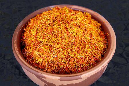 Saffron spice in pot isolated on black