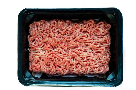 Raw minced meat on a plastic black plate, white isolated background