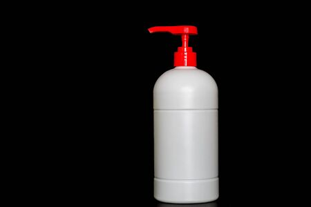 White plastic pushing pump bottle isolated on black background, copy space advertising text area 版權商用圖片