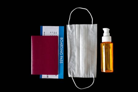 Virus prevention and travel concept during epidemic disease (Covid-19) Protective mask, hand disinfectant, sanitizer, passport and flight ticket, isolated black background