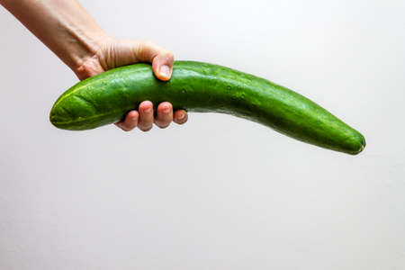 Woman hand holding big cucumber on white background 版權商用圖片