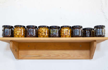 Green and black olives in glass jar, on wooden shelf 版權商用圖片