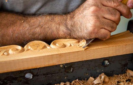 Carpenter working on wooden furniture with hand carving. Wood carving art with hand tools 版權商用圖片