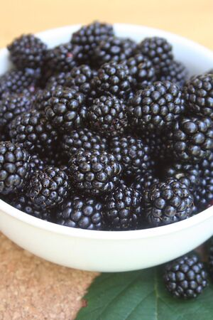 Ripe blackberries in a ceramic bowl on a wooden background. Selective focus Stock Photo
