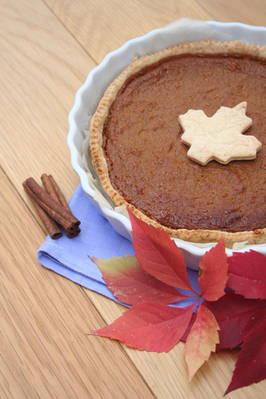 Homemade Pumpkin Pie for Thanksgiving Day with Autumn Decorations on Wooden Table Stock Photo
