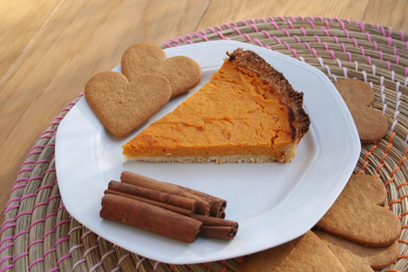 Slice of Pumpkin pie with cinnamon on a plate on a wooden table
