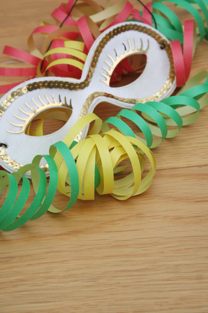 Colorful carnival streamers and white and golden mask on wooden background Stock Photo