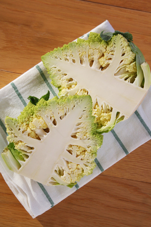 Half cut of fresh Romanesco broccoli or Roman cauliflower on wooden table. Brassica oleracea Banco de Imagens