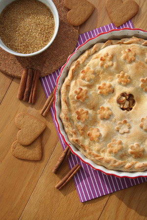 homemade apple pie with cinnamon and cookies on wooden table