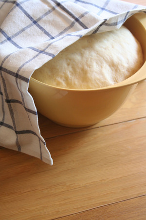 Bread dough rising in a yellow plastic bowl on wooden table