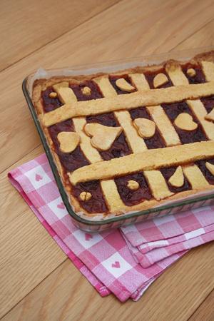 Homemade cherry jam tart or pie on wooden table