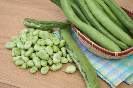 Fresh broad beans on a wooden table Imagens