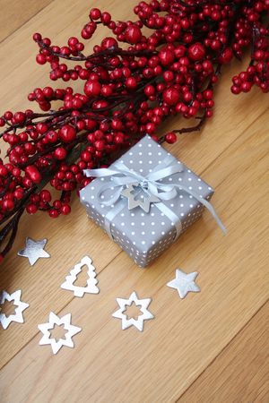 Christmas silver gift box with red berries decoration on wooden table Imagens