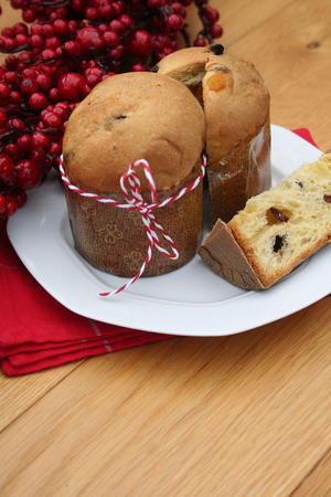 Italian Christmas cake called Panettone with red berries decoration on wooden table. Traditional food to celebrate Christmas holidays
