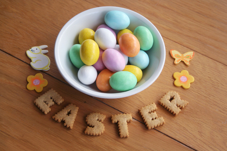 Easter eggs in a bowl with cookies on wooden background Stock Photo