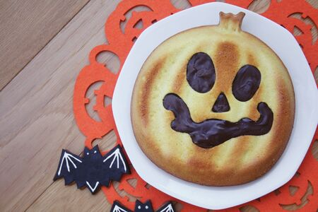 Halloween cake in shape of a pumpkin with chocolate decoration on wooden table. Halloween sweet food