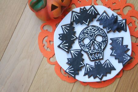 Halloween cookies in shape of skull and bat on a plate on wooden background. Halloween sweet food