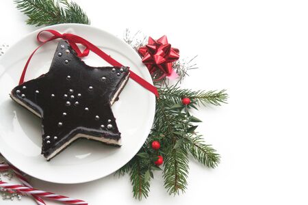 Christmas dessert. Homemade cheesecake in shape of star on a plate isolated on white with decorations and pine branches Stockfoto