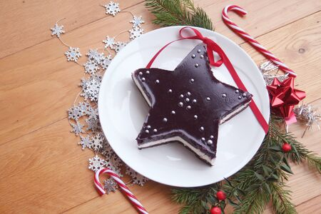 Christmas dessert. Homemade cheesecake in shape of a star on a wooden table with decorations and pine branches