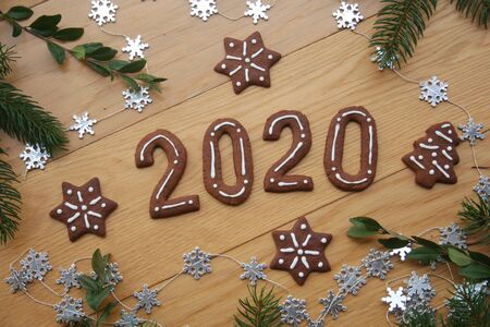 New Year's Eve background. Homemade chocolate cookies in shape of 2020 on a wooden table with pine branches and silver stars